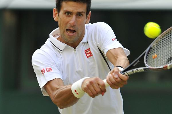 Novak Djokovic returns against Jeremy Chardy in their third round match.