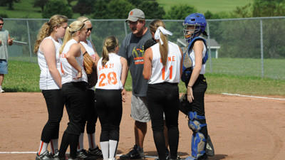 Coach Craig Stinebiser talks to his infield early in game one of a LHYL junior softball doubleheader Saturday.