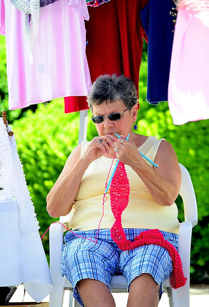 Eloise Plank knits a prayer shawl Saturday while waiting for customers at Faire off the Square at North Potomac Street parking lot.