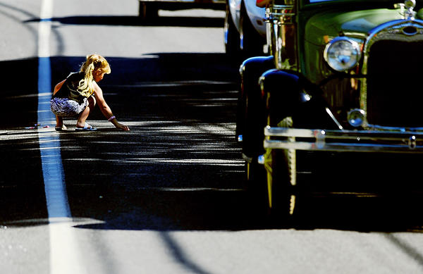 Trinity Hoover, who is visiting from Meyersdale, Pa., snags pieces of candy tossed from passing antique cars during Saturday morning's parade in Blue Ridge Summit, Pa. The parade kicked off the Mountaintop Heritage Days festival at nearby Fort Ritchie.
