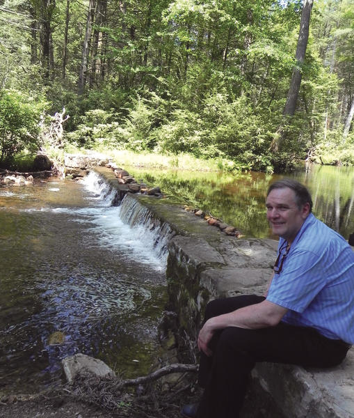 Ross Hetrick, president of the Thaddeus Stevens Society, sits near the dam that was used to power the original Caledonia Ironworks operation.