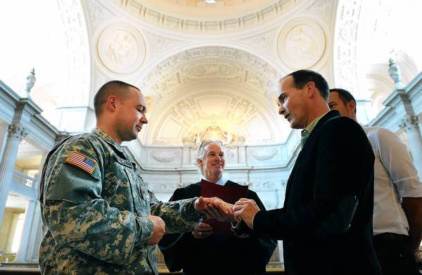 Army Sgt. Michael Potoczniak, left, and his partner, Todd Saunders, exchange rings during their marriage ceremony at San Francisco City Hall on Saturday.