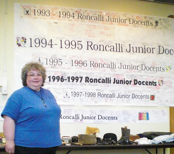 Sherri Rawstern, curator of education at the Dacotah Prairie Museum, stands in front of the class banners for the museum's Junior Docent program, now celebrating its 20th year.