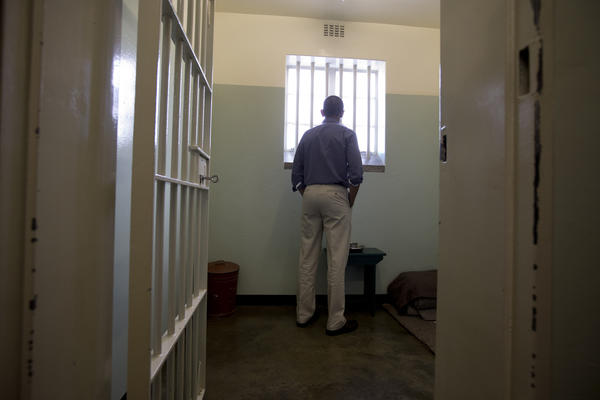 President Obama looks out the window of Nelson Mandela's cell on Robben Island, where the anti-apartheid leader was imprisoned for 18 years,