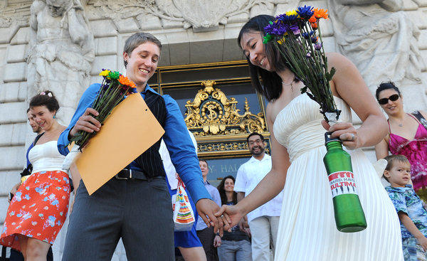 Carey Myslewski, left, and Katy Yan walk out of City Hall a married couple Saturday in San Francisco.