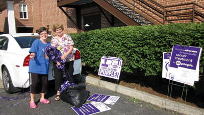 Amy Berkey and Linda Malisko work on the purple ribbons and signs that were distributed throughout Windber Borough on Monday night as part of this year's Relay For Life. Malisko, along with Joanne Wright, are co-chairwomen of the Paint the Town Purple event.
