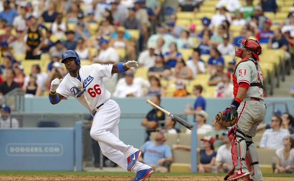 Yasiel Puig hits a triple as Philadelphia Phillies catcher Carlos Ruiz looks on during the fifth inning of the Dodgers' 6-1 victory.