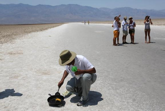Randy Thomas of Vacaville, Calif., tries to fry an egg on the salt flats in Death Valley's Badwater Basin. He drove there to experience the heat.