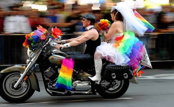 Veterans of San Francisco's gay pride parade said the crowd was louder and happier than usual, and probably even bigger, surpassing the typical turnout of 1 million. Above, a couple show their colors on a motorcycle during the parade on Market Street.