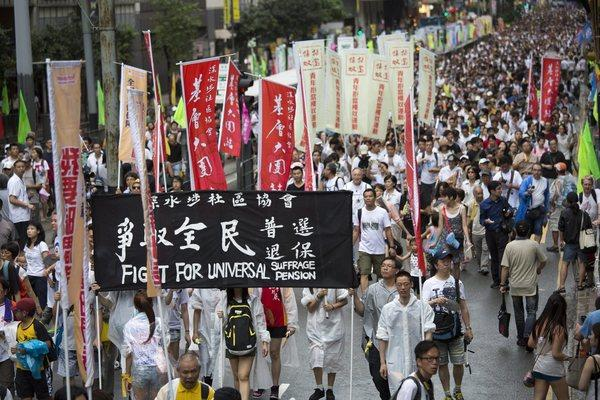 """Protesters march during a rally in Hong Kong, calling for """"one person, one vote"""" and universal suffrage in the scheduled 2017 election of a chief executive."""