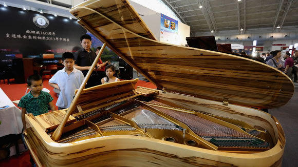 Consumers visit the Steinway & Sons piano zone at the Luxury China 2013 exhibition last month in Beijing.