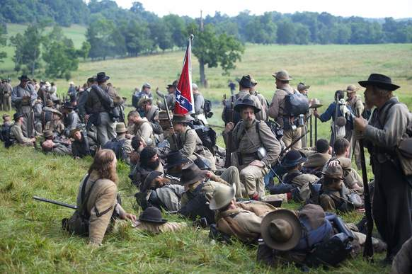 Actors playing Confederate soldiers congregate at a wood's edge awaiting ord