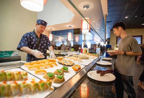 Sushi chef Pian Ling, left, prepares fresh items for customers during Grande Buffet and Grill's grand openiing June 28. The restaurant has multiple buffet stations and seating for 500.
