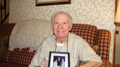 Arnold Benford, Somerset, holding a photograph of he and his wife, Beverly, with former President George H.W. Bush.