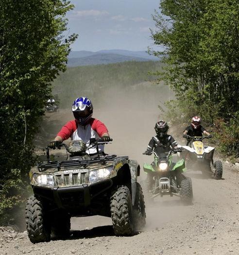 A family rides on ATVs