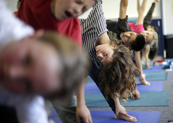 Students hold a position during a yoga class at Capri Elementary School in Encinitas. A judge has ruled against a claim that teach yoga in Encinitas schools does not amount to religious instruction and can continue.