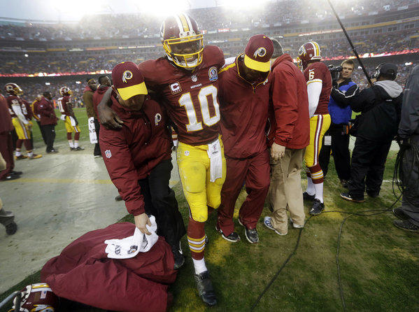 Washington Redskins quarterback Robert Griffin III is helped off the field after an injury during the second half of a game in December against the Baltimore Ravens in Landover, Md. The league has disavowed any effort to help promote the new health insurance subsidies created by the 2010 federal healthcare law, a.k.a. Obamacare.