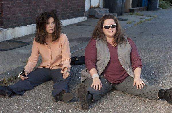 "FBI Special Agent Sarah Ashburn (Sandra Bullock), left, and Boston Detective Shannon Mullins (Melissa McCarthy) sit in shock after an unexpected setback in ""The Heat."""