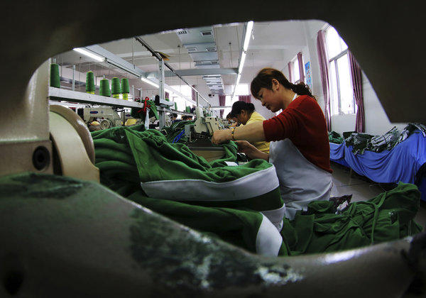 China's manufacturing sector weakened again in June amid a credit crunch and a decline in U.S. and European orders. Above, workers sew fabrics at a garment factory in Jiujiang in central China's Jiangxi province.