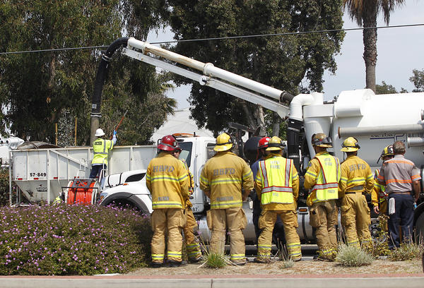 Huntington Beach firefighters monitor the scene where a non-toxic material used for fertilizer for non-food crops is moved after a truck tipped over on Brookhurst Street near Bushard in Huntington Beach on Monday.