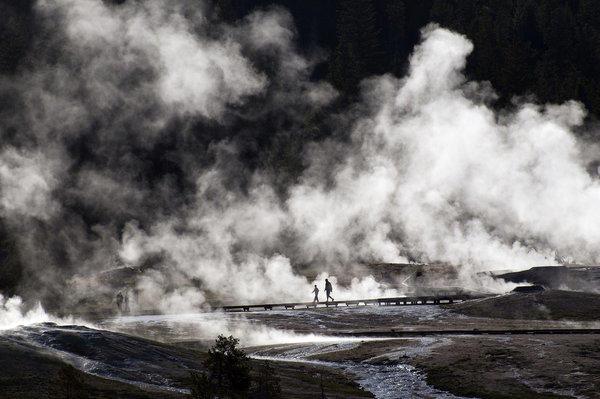 Visitors walk along boardwalks near the Old Faithful geyser in Yellowstone.