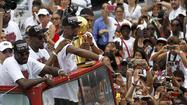 Miami Heat's Anthony and Cole look on as teammate Bosh holds the trophy during the Heat's NBA Basketball Championship celebratory parade in Miami