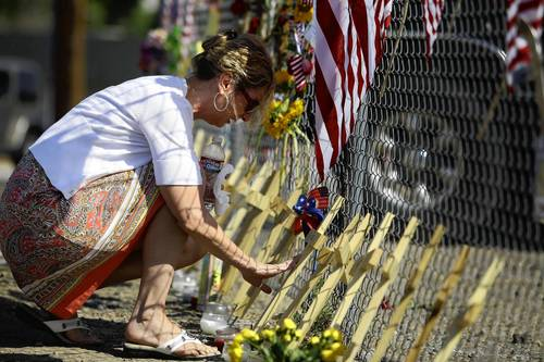 Linda Lambert touches the cross displayed for her nephew and Hot Shot Firefighter Andrew Ashcraft, at a makeshift memorial for the 19 firefighters who perished battling a fast-moving wildland fire, outside the Granite Mountain Interagency Hot Shot Crew fire house in Prescott, Arizona. Weary crews on Tuesday looked for a break in the weather to gain ground against a fierce Arizona wildfire that has already killed 19 of their fellow firefighters in the worst wildland fire tragedy in 80 years.