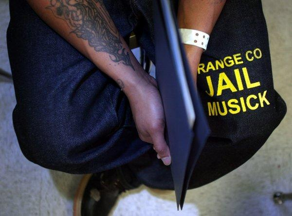 """A bill before California lawmakers seeks to eliminate the question """"Have you ever been convicted of a crime?"""" from applications for public employers. Above: An inmate holds papers collected at a job fair at the James A. Musick Correctional Facility in Orange County."""