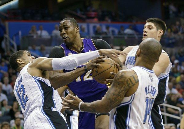 Lakers center Dwight Howard struggles to get to the basket while guarded by three Orlando Magic players.