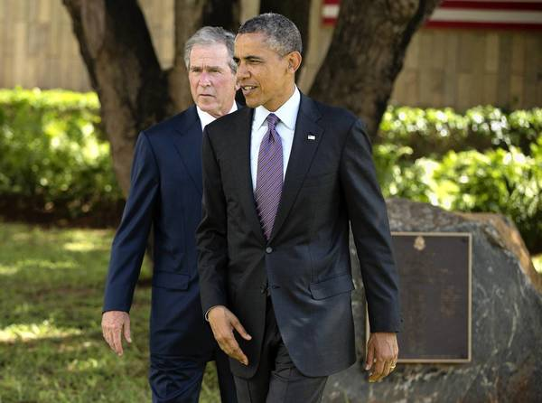 President Obama and former President George W. Bush make their way to speak with family members of victims of the 1998 U.S. Embassy bombing in Dar es Salaam, Tanzania.