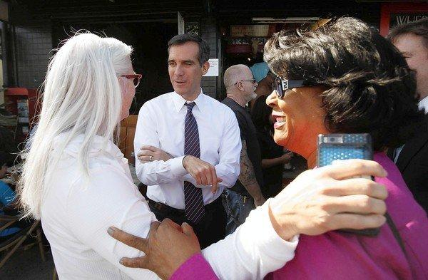 Then-Los Angeles City Councilman Eric Garcetti talks with supporter Kim Norris, left, and then-Councilwoman Jan Perry during a campaign stop while running for mayor.