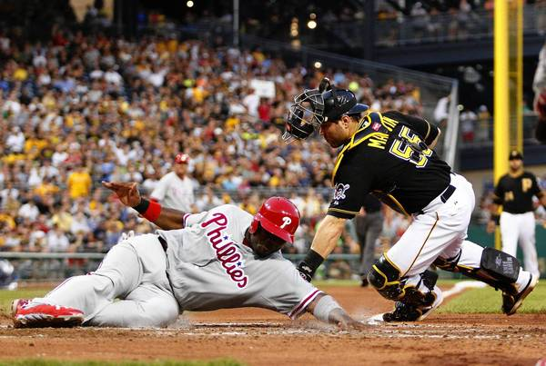 Ryan Howard #6 of the Philadelphia Phillies scores on a play at the plate against Russell Martin #55 of the Pittsburgh Pirates in the sixth inning during the game on July 2, 2013 at PNC Park in Pittsburgh, Pennsylvania.