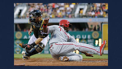 Philadelphia Phillies' Ryan Howard, right, slides around Pittsburgh Pirates catcher Russell Martin to score during the sixth inning of a baseball game in Pittsburgh on Tuesday. Howard scored on a double by Delmon Young.