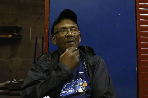 Jimmy Rogers, general manager of the Brixton Topcats in the London Borough of Lambeth, watches practice from behind his cluttered table at the end of the court last summer.