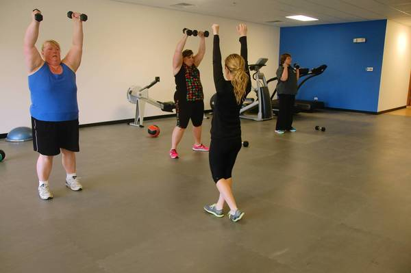 Trainer Jillian McAfee works with Diane Reiter of Aurora, from right, Genie Przybylski of Oswego and Kim Tremblay of Bolingbrook at the new Downsize Fitness gym that opened in Naperville this week.