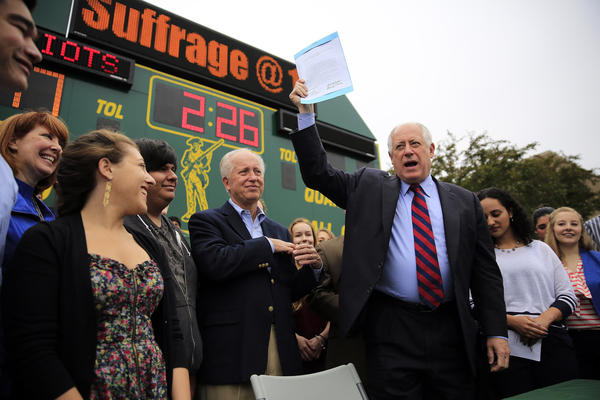 On the football field at Adlai E. Stevenson High School in Lincolnshire, Gov. Pat Quinn waves the bill allowing voting rights in primaries to 17-year-olds who will be 18 by the time of the general election.