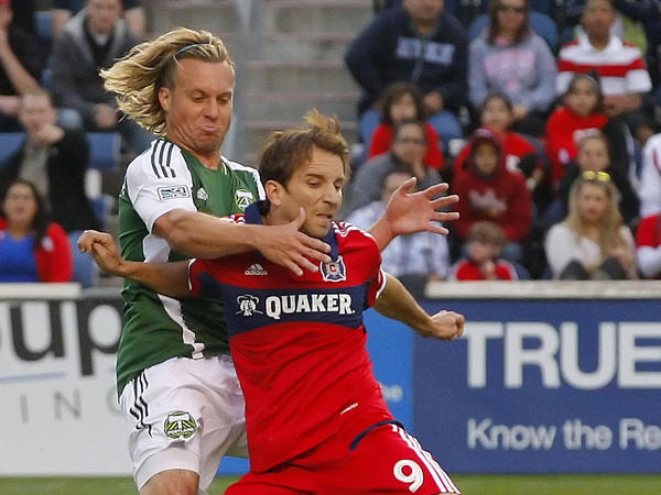 Chicago Fire midfielder Mike Magee (9) battles Portland Timbers defender/midfielder Michael Harrington for the ball during a game at Toyota Park.