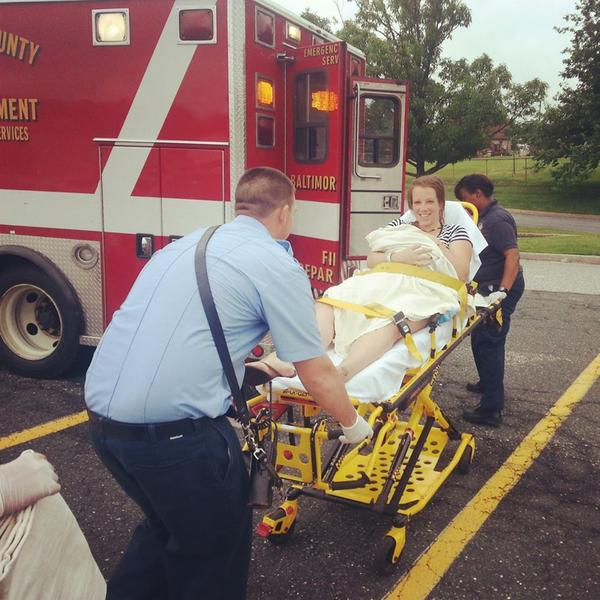 Amber Noll, holding her brand-new baby girl Ava, are wheeled to an ambulance after mom gave birth in a Kmart parking lot.