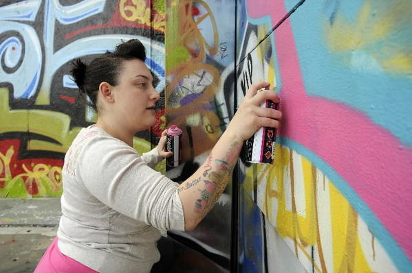 Dina Brass of Hartford spray-paints a wall at Heaven downtown skate park.