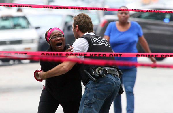Nicole Jones, the victims sister, is restrained by police at the scene of a shooting at 87th Loomis Avenue in Chicago.
