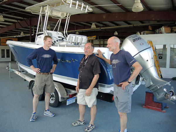 Boyne Boat Yard chief operations officer Robert Linn (center) entertains owners Ben (left) and Steve Van Dam (right) with his stories. They are standing in front of the first boat they have to broker, a Pro Line 230 Sport.