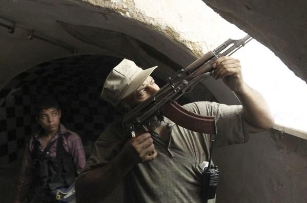 A Free Syrian Army fighter aims his weapon as he takes a defensive position in the old city of Aleppo on July 3