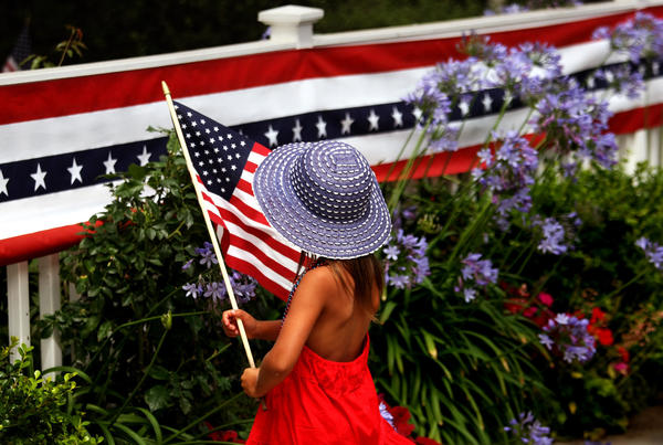 Marlo Harris, 4, waves the American flag while walking past a white picket fence decorated for Fourth of July celebrations in Pacific Palisades.