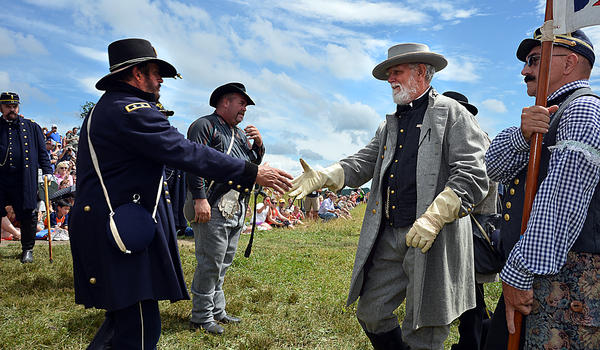 Union Major General George G. Meade, enacted by Steve Weatherbee, left, extends his hand to Confederate General Robert E. Lee, portayed by George Wells, Wednesday during Picketts Charge Commemorative March at Gettysburg National Military Park.