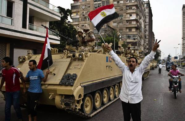Egyptians salute Army tanks upon their deployment on a street leading to Cairo University.