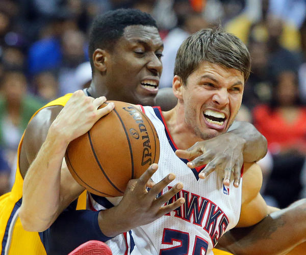The Hawks' Kyle Korver and Pacers' Ian Mahinmi battle for a ball on a floor scramble during the second half of Game 6.