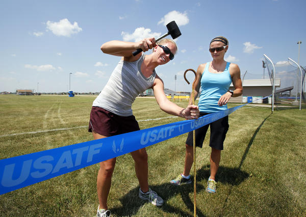 Megan Betz, left, uses a hammer to set a stake as she and Lynne Nacke put up boarder tape near the discus area at Swisher Field Wednesday. The pair of Northern State University Track coaches were working on preparations for the USATF track meet that begins today. Nacke, the meet director, said over 1,000 athletes will compete in the four-day event. American News Photos John Davis