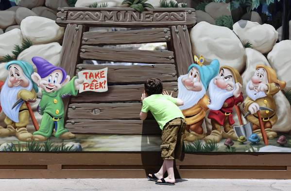Guests peer through a construction wall, illustrated with images of the Seven Dwarfs, at the site of The Seven Dwards Mine Train, being built in New Fantasyland at the Magic Kingdom, Walt Disney World.