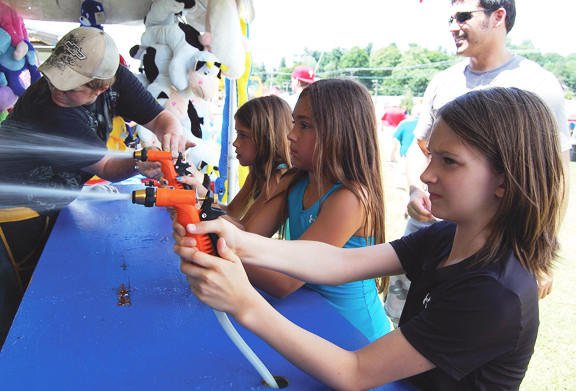 Alina Myers, 11, right, plays a water game at Summer Jubilee in Waynesboro, Pa., with her friends Alexa Fortmann and Olivia Fortmann.