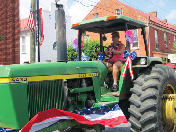 Jefferson County Commissioner Jane Tabb pilots a John Deere tractor through the streets of Shepherdstown, W.Va., for Thursday's Fourth of JUly Parade.